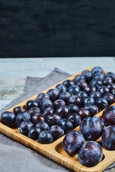 Prugne da giardino sul piatto di legno e su sfondo scuro. foto di alta qualità