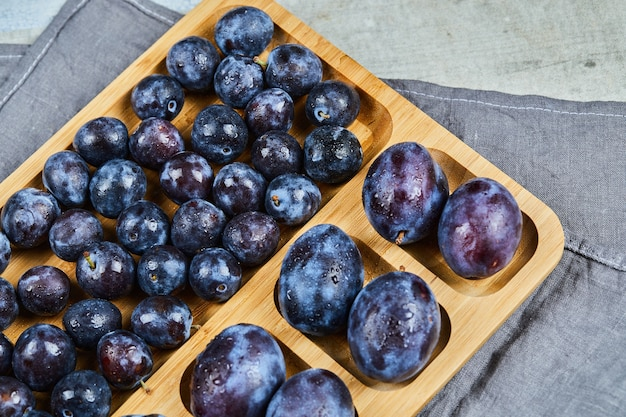 Garden plums on wooden platter with gray tablecloth