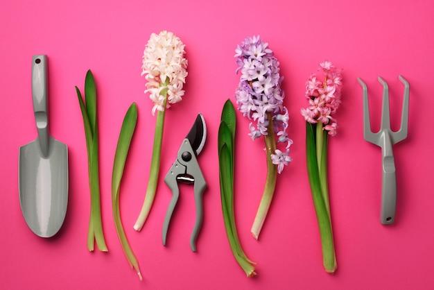 Садовый секатор, грабли, с цветами на розовом перламутровом фоне.