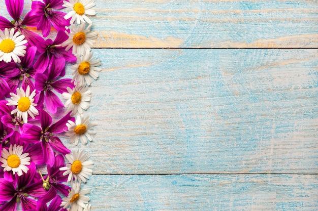 コピースペースを持つ青い古い木製のテーブル背景に庭の紫と白の花、