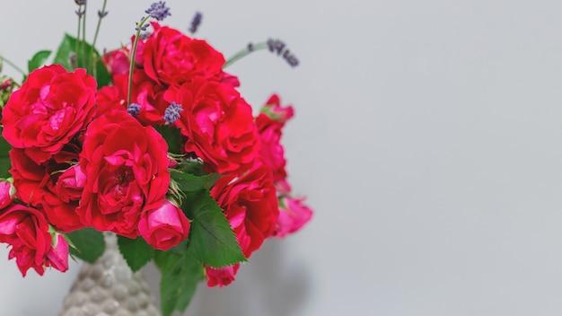 繊細な花が咲くミニマルなインテリア春の素朴な背景の灰色の花瓶の庭のバラ