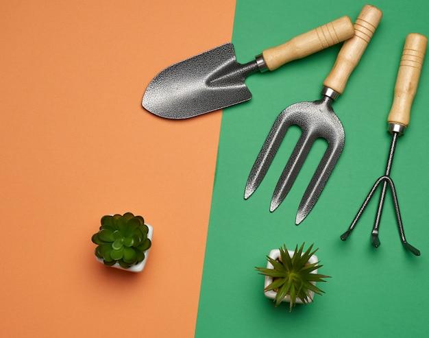 Садовый набор лопат, граблей, вил на зелено-оранжевом фоне, вид сверху