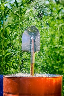 Garden shovel in a barrel of water in small splashes of water