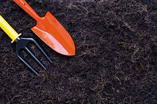 Garden shovel and fork on soil with coconut shell's hair for agriculture.