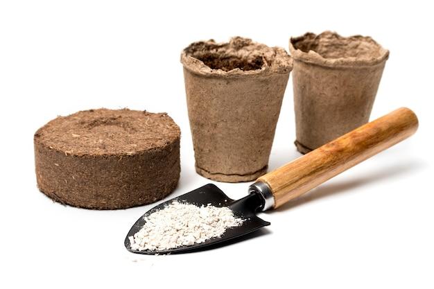 ミネラル肥料、ピートポット、白地にピートタブレットのクローズアップを備えたガーデンシャベル。