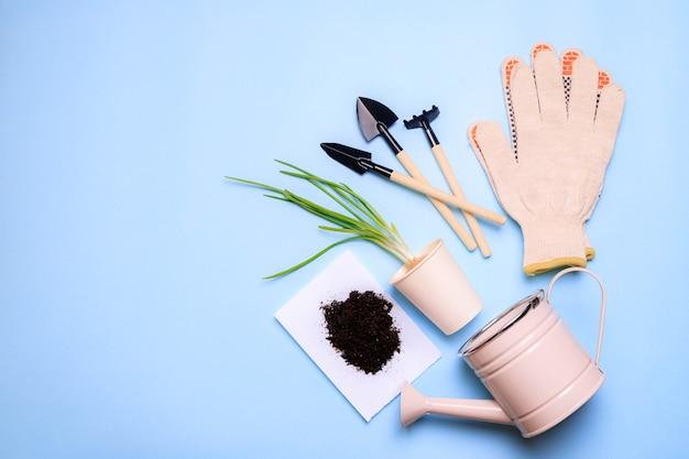青い背景の庭のシャベル。ガーデニングのレイアウト。春の植え付け。植物の世話。地面で作業します。青い背景。スペースをコピーします。庭の手袋と地球。