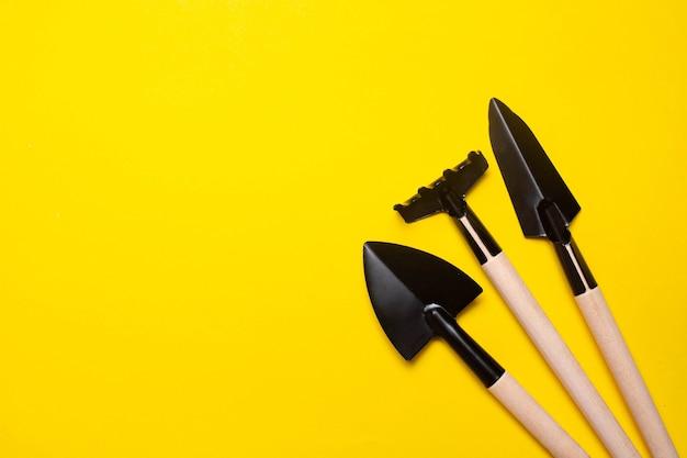 Садовые лопаты на желтом фоне. план садоводства. весенняя посадка. уход за растениями. работа в земле. желтый фон. скопируйте пространство.