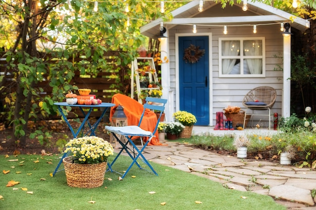 Садовый стол и стулья с яблоками и тыквами на осеннем дворе. хэллоуин. внутренний уютный дворик