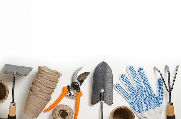 園芸工具および白い背景の上の手袋。テキスト用のスペース
