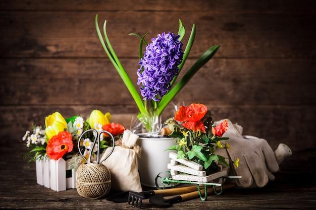 木製の背景の上に花のためのガーデンツール