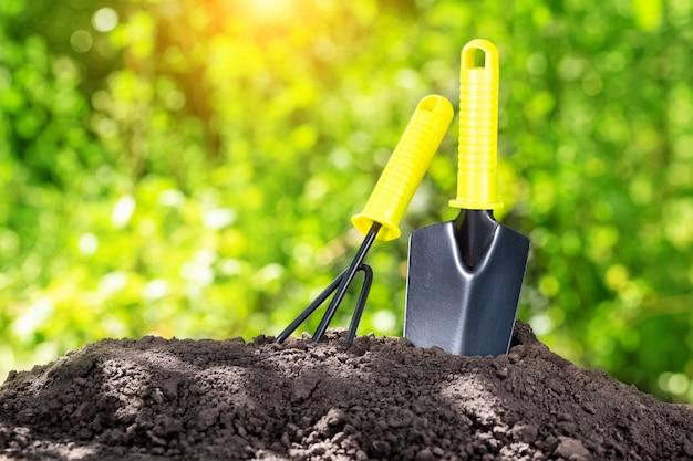 Садовые инструменты в кучу земли против листвы