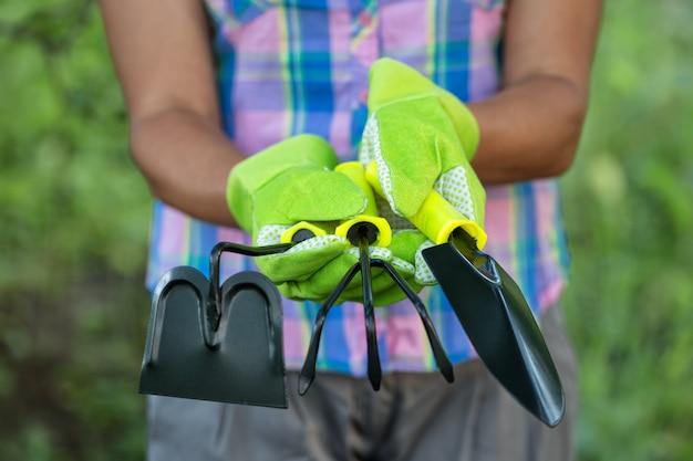 女性農家の手の中の園芸工具