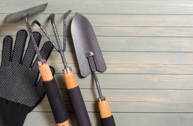 Garden tools on a light wooden background. flat top view