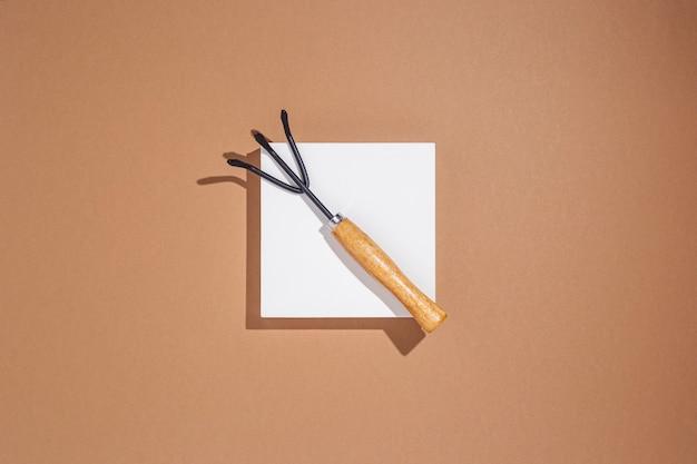 갈색 배경에 흰색 사각형 연단에 누워 정원 도구. 평면도, 평면도.