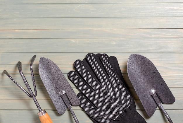 明るい木製の背景の園芸工具。