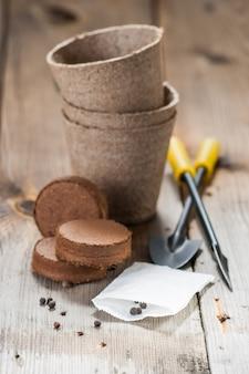 ガーデンツール、泥炭ポット、木製のテーブルの種子