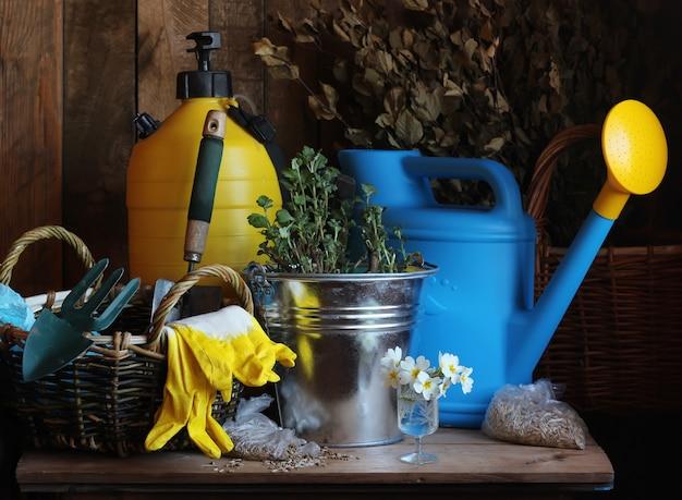 Садовый инвентарь, лейка, лопата, ведро, перчатки, мусор на столе.