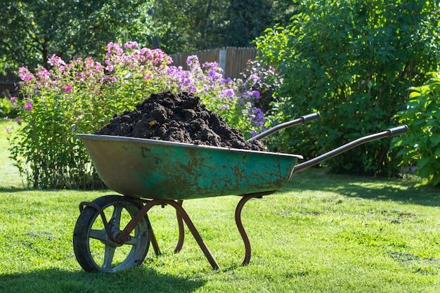 Garden-wheelbarrow filled with soil on a farm.