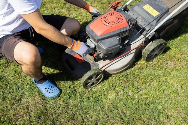 Garden worker checks lawn mower before mowing grass