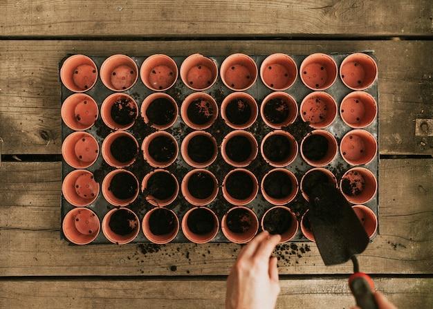 庭師が植木鉢に土を追加するフラットレイ
