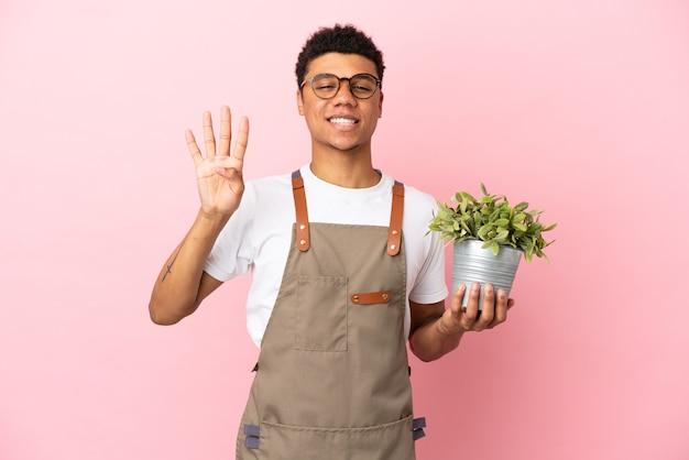 Садовник африканский мужчина держит растение, изолированное на розовом фоне, счастлив и считает четыре пальцами