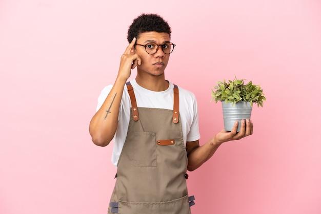 Садовник африканский мужчина держит растение, изолированное на розовом фоне, думая об идее