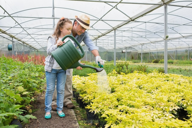 庭師と孫娘が植物に水をかける