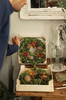 Gardener arranging floral wreaths in boxes