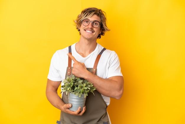 고립 된 식물을 들고 정원사 금발 남자