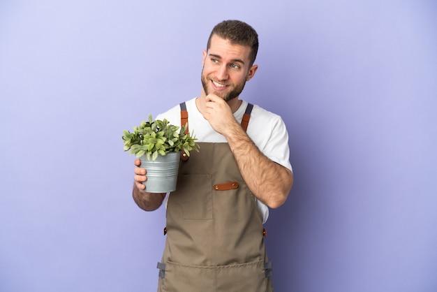 Кавказский мужчина садовник держит растение, изолированное на желтом фоне, смотрит в сторону и улыбается