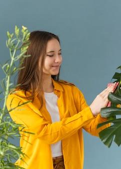 Садовник чистит листья растения
