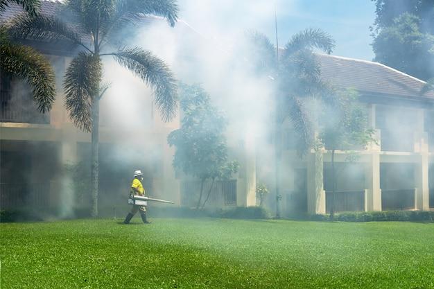 Садовник делает отравление, распыляя инсектициды или пестициды для борьбы с насекомыми в отеле.