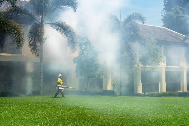 Gardener doing a poisoning activity by spraying insecticide or pesticides to control the insects in a hotel.