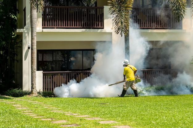 A gardener doing a poisoning activity by spraying insecticide or pesticides to control the insects in a hotel.