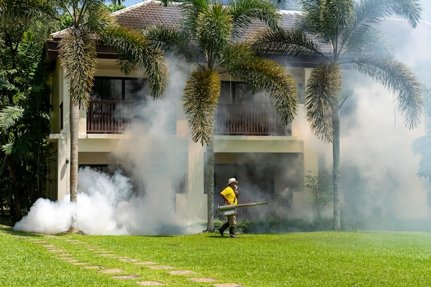 A gardener doing a poisoning activity by spraying insecticide or pesticides to control the insects in a hotel