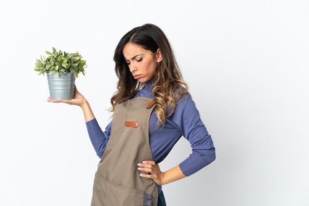 Девушка-садовник держит растение, изолированное на белой стене, страдает от боли в спине из-за того, что приложила усилие