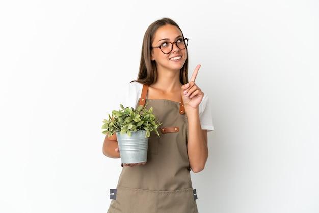 좋은 아이디어를 가리키는 고립 된 식물을 들고 정원사 소녀