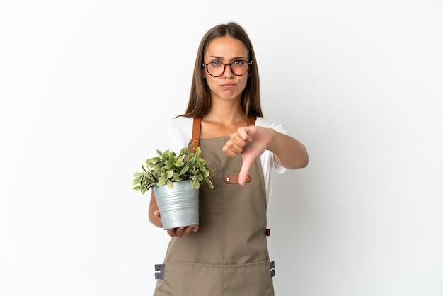 부정적인 표현으로 아래로 엄지를 보여주는 고립 된 식물을 들고 정원사 소녀