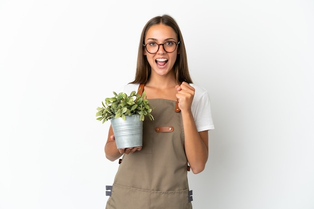 勝者の位置での勝利を祝う孤立した白い背景の上に植物を保持している庭師の女の子