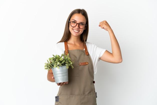 강한 제스처를 하 고 격리 된 흰색 배경 위에 식물을 들고 정원사 소녀