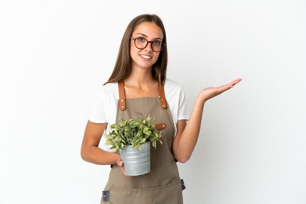 고립 된 흰색 배경 위에 식물을 들고 정원사 소녀와 서 초대에 대 한 손을 확장