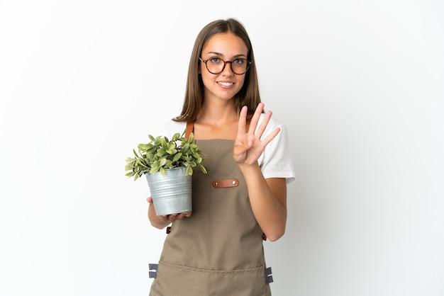幸せな孤立した白い背景の上に植物を保持し、指で4を数える庭師の女の子