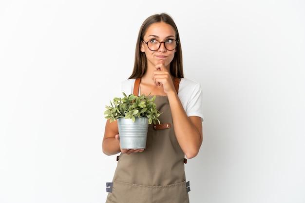 의심과 생각을 갖는 고립 된 흰색 배경 위에 식물을 들고 정원사 소녀