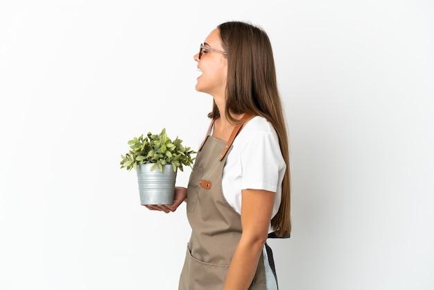 측면 위치에 웃고 고립 된 흰색 배경 위에 식물을 들고 정원사 소녀
