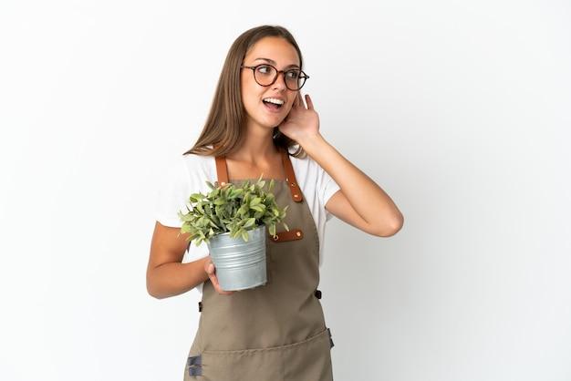귀에 손을 넣어 뭔가를 듣고 격리 된 흰색 배경 위에 식물을 들고 정원사 소녀