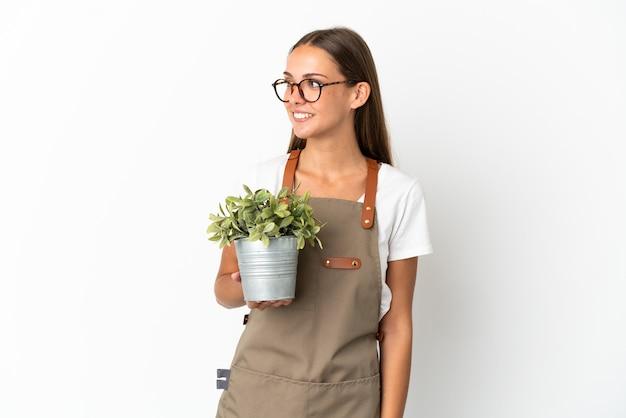 側を見て孤立した白い背景の上に植物を保持している庭師の女の子