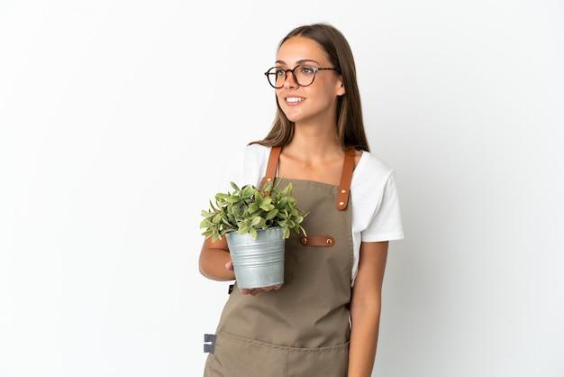 격리 된 흰색 배경 위에 식물을 들고 정원사 소녀 측면을 찾고 웃