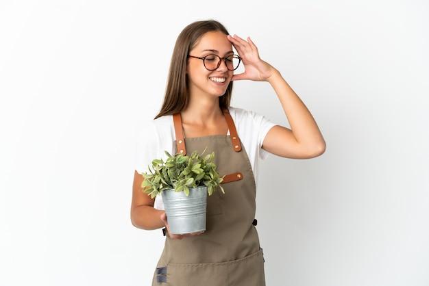 たくさん笑って孤立した白い背景の上に植物を保持している庭師の女の子