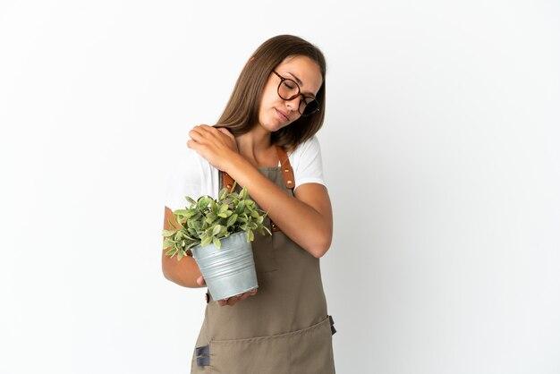 노력을 한 데 대한 어깨에 통증으로 고통 격리 된 흰색 배경 위에 식물을 들고 정원사 소녀