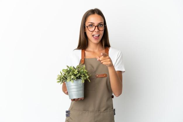 孤立した白い背景の上に植物を保持している庭師の女の子は驚いて正面を指しています